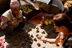 Okkernoothandelaar op de straten van Katmandu, Nepal met klant Stock Foto's
