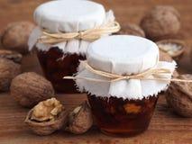 Okkernoten, amandelen en honing in kruiken Stock Foto's