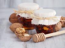 Okkernoten, amandelen en honing in kruiken en honingsdipper Royalty-vrije Stock Afbeelding