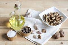Okkernoten in een witte kom, een knoflook, een peperzout en een olie op een houten achtergrond, een houten raad en een wit servet Royalty-vrije Stock Foto