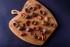 Okkernoten en droge vruchten op een houten raad, hoogste mening Stock Foto