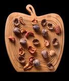 Okkernoten en droge vruchten op een houten raad, hoogste mening op zwarte backgound Royalty-vrije Stock Fotografie