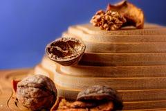 Okkernoten en droge vruchten op een houten steun in de vorm van een piramide Stock Foto's
