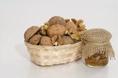 Okkernoten in houten mand en notenjam Stock Fotografie