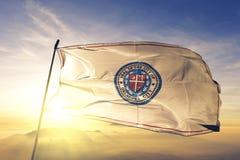 Oklahoma City-Hauptstadt von Oklahoma des Flaggentextilstoffgewebes Vereinigter Staaten, das auf den Spitzensonnenaufgangnebelneb stockfotos