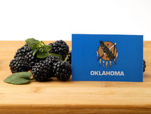 Oklahoma flag on a wooden panel with blackberries isolated on a Stock Photography