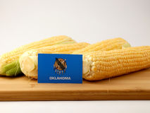 Oklahoma flag on a wooden panel with corn isolated on a white ba Royalty Free Stock Image