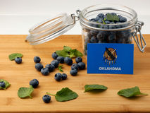 Oklahoma flag on a wooden plank with blueberries  on whi Royalty Free Stock Image