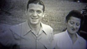 OKLAHOMA, LOS E.E.U.U. - 1943: Hombre que salta con las mujeres como ellos más allá de su coche querido almacen de video