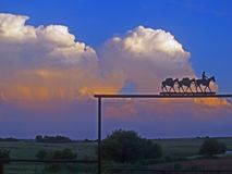 Reflection of the sunset in the clouds behind the packtrain on the gate. Stock Image
