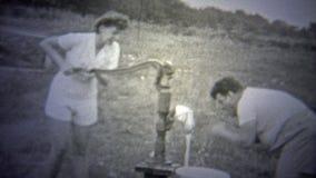 OKLAHOMA, usa - 1943: Kobieta pompuje well podczas gdy mężczyzna myje zbiory