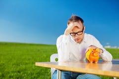 Oklapnięty mężczyzna patrzeje jego prosiątko banka Fotografia Stock