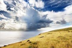Oklarheter över havet och den gröna kullen i påskön Royaltyfri Foto