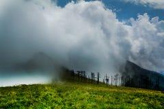 Oklarheter och högt berg Arkivbilder