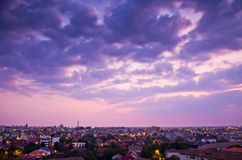 Oklarheter och stad efter solnedgång royaltyfria foton