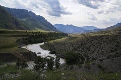 oklarhetsberg över område Blå himmel och grönt gräs i dalen av en bergflod Royaltyfri Fotografi