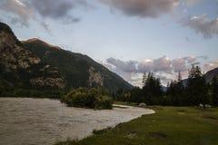 oklarhetsberg över område Blå himmel och grönt gräs i dalen av en bergflod Arkivbilder