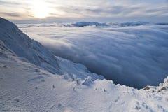 oklarhetsberg över solnedgångvinter Arkivbild