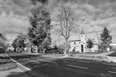Okna, Litomerice区,捷克共和国- 2017年10月13日:与路在前景和教堂的秋季村庄广场backgro的 免版税库存照片