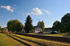 Okna, Ceska Lipa district, Czech republic - July 14, 2018: small train station, trees, parked cars, train and people during sunny. Evening Royalty Free Stock Images