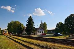 Okna, distrito de Ceska Lipa, República Checa - 14 de julio de 2018: la pequeña estación de tren, árboles, parqueó los coches, el Imágenes de archivo libres de regalías