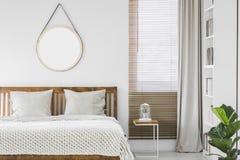 Okno z drewnianymi storami i jasnopopielatą zasłoną w białym bedroo fotografia stock