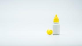 Oko kropel butelka z otwartą żółtą nakrętką odizolowywającą na białym tle z pustą etykietki i kopii przestrzenią obrazy royalty free