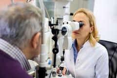 Oko lekarki checkup ono przygląda się z aparatem zdjęcia stock