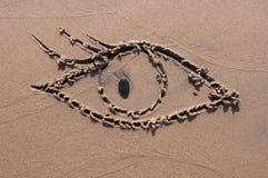 Oko rysujący w piasku beach tło Zdjęcie Stock
