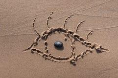 Oko rysujący w piasku beach tło Fotografia Royalty Free