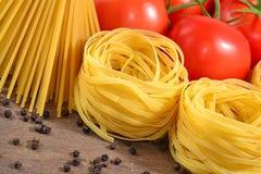 Okokt italiensk pasta, mogna tomater förgrena sig och svartpeppar Arkivfoto