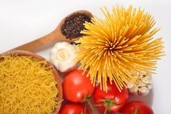 Okokt italiensk pasta, mogna tomater förgrena sig och svartpeppar på Arkivfoto