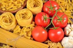 Okokt italiensk pasta, mogna tomater förgrena sig, och vitlök Royaltyfria Bilder