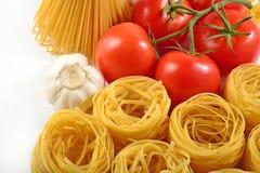 Okokt italiensk pasta, mogna tomater förgrena sig, och vitlök Arkivfoto