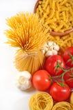 Okokt italiensk pasta, mogna tomater förgrena sig och vitlök på en whi Arkivbild
