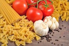 Okokt italiensk pasta, mogna tomater förgrena sig, vitlök och svart p Royaltyfri Bild