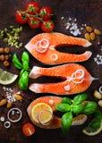 Okokt laxfiskfilé med aromatiska örter, lök, avokado, broccoli, pepparklocka, grönsaker på träbakgrund royaltyfri fotografi