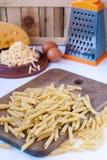 Okokt pasta och grated ost Arkivbilder