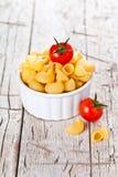Okokt pasta och körsbärsröda tomater i en bunke Royaltyfria Foton