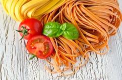 Okokt röd och gul italiensk pasta med basilikakopieringsutrymme Royaltyfria Bilder