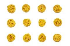 Okokt rullande traditionell italiensk pasta på vit bakgrund som isoleras Del av rå fettuccine eller tagliatelle royaltyfria foton