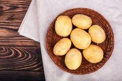 Okokta potatisar på en träbakgrund Potatisknölar i en brun korg på ett grått stycke av torkduken Healthful lantliga grönsaker royaltyfria foton