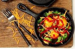 Okokta rå ägg i kastrullen med Brocolli, ost och Sriracha Royaltyfria Bilder