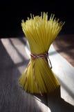 Okokta vermicellernudlar som binds med radanseende på en wood skärbräda Arkivfoton