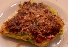 Okonomiyaki - ιαπωνική τηγανίτα με το μπέϊκον και το λάχανο, μια πικάντικη σάλτσα και ψεκασμένος με την παλαμίδα στοκ φωτογραφία με δικαίωμα ελεύθερης χρήσης