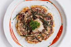 Okonomiyaki is a Japanese savoury pancake containing a variety of ingredients.  Stock Photos