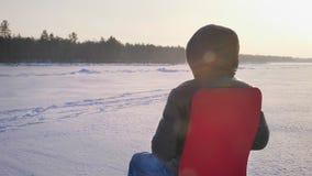 Okrążać wokoło strzału samotny biznesmen w ciepłym żakieta i kapiszonu obsiadaniu na czerwonym krześle na śnieżnego pola tle zbiory wideo