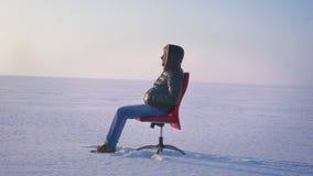 Okrążać wokoło strzału samotny biznesmena obsiadanie na czerwonym krześle i dopatrywanie w odległość na śnieżnego pola tle zbiory wideo