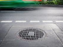 Okrąża ośniedziałą żelazną manhole pokrywę na drogowej podłoga Fotografia Stock