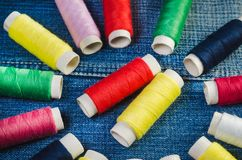 Okrąg barwione nici cewy z centrum czerwone i żółte niciane cewy na drelichu zdjęcie stock
